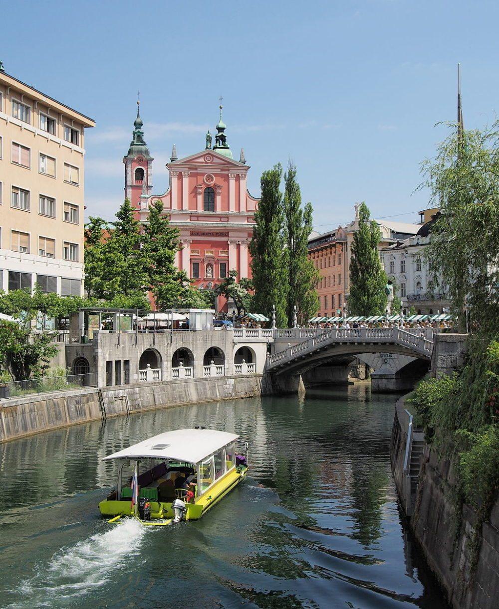 """Der Fluss Ljubljanica, im Hintergrund die Drei Brücken (Tromostovje). (Urheber: Petar Milošević / Wiki / Lizenz: <a href=""""http://creativecommons.org/licenses/by-sa/3.0/deed.en"""" target=""""_blank"""">CC</a>)"""