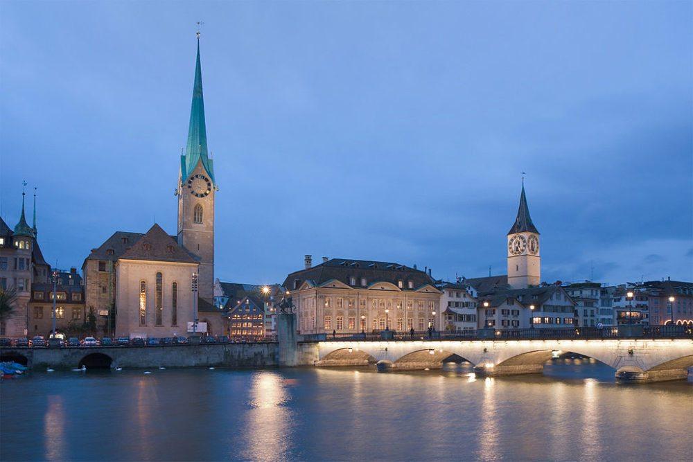 Zürich bei Nacht: Fraumünster, Zunfthaus zur Meisen, Münsterbrücke, Sankt Peter-Kirchturm (Bild: Ikiwaner, Wikimedia, CC)