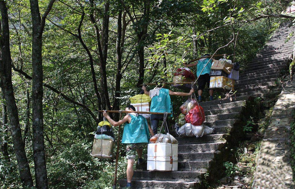 Träger bringen im Huang Shan Gebirge schwere Lasten eine Treppe zu einem Hotel auf etwa 1500 m hinauf (Bild: Arne Hückelheim, Wikimedia, CC)