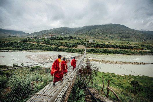 Mönche wandern über eine Brücke (Bild: © Dylan Haskin - shutterstock.com)