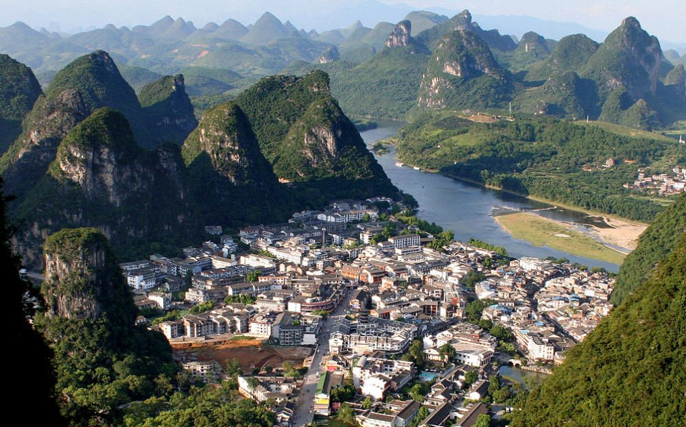 Stadt Yangshuo mit dem Li-Fluss im Hintergrund (Bild: Ericbolz, Wikimedia)