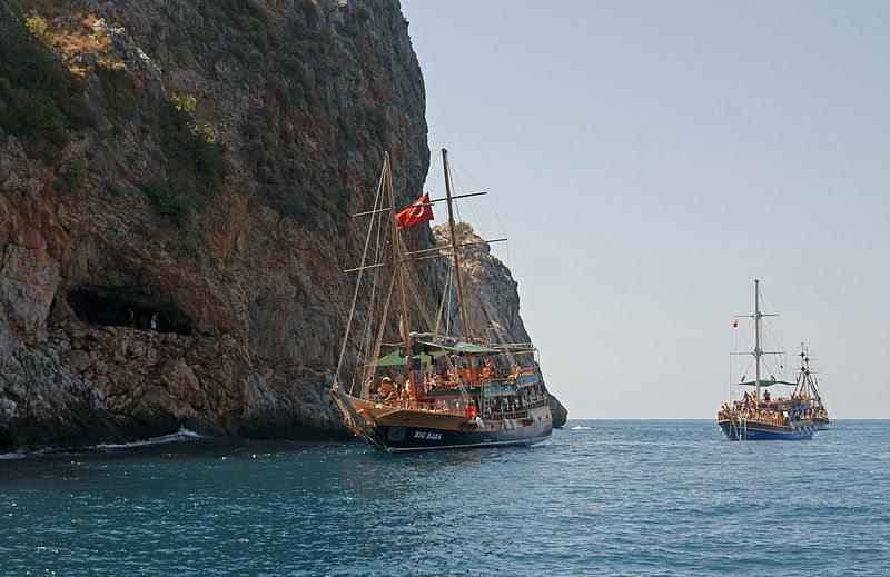 Ausflugsboote und Klippenspringer an der Aşıklar-Höhle (© kallerna / Wikimedia / CC)