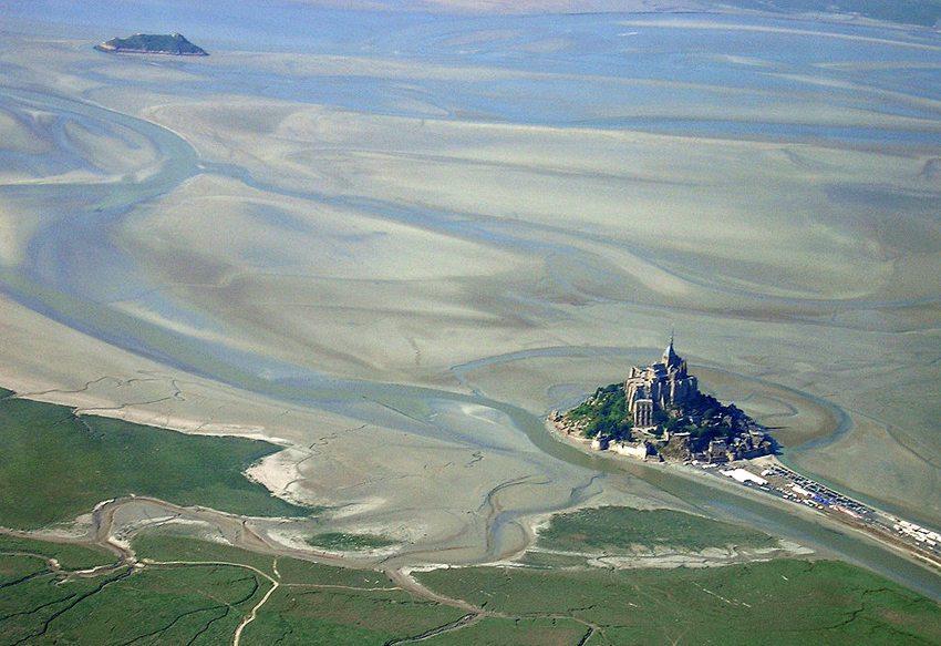 Mont Saint-Michel und Tombelaine aus der Luft, vor Beginn der Umbauarbeiten am Damm 2006 (Bild: Uwe Küchler, Wikimedia, GNU)