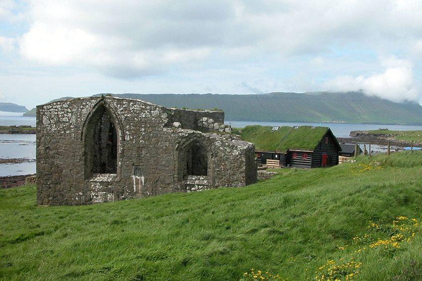 Die Ruine der Magnuskathedrale von Kirkjubøur, im Hintergrund – der traditionsreiche Hof aus dem 11. Jahrhundert, Färöer-Inseln. (Bild: Erik Christensen, Wikimedia, GNU)