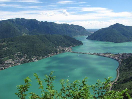 Der Luganer See gehört nicht zuletzt aufgrund seiner herrlichen Umgebung zu den beliebtesten Reisezielen im Grenzgebiet zwischen der Schweiz und Italien. (Bild: © lenisecalleja.photography - shutterstock.com)
