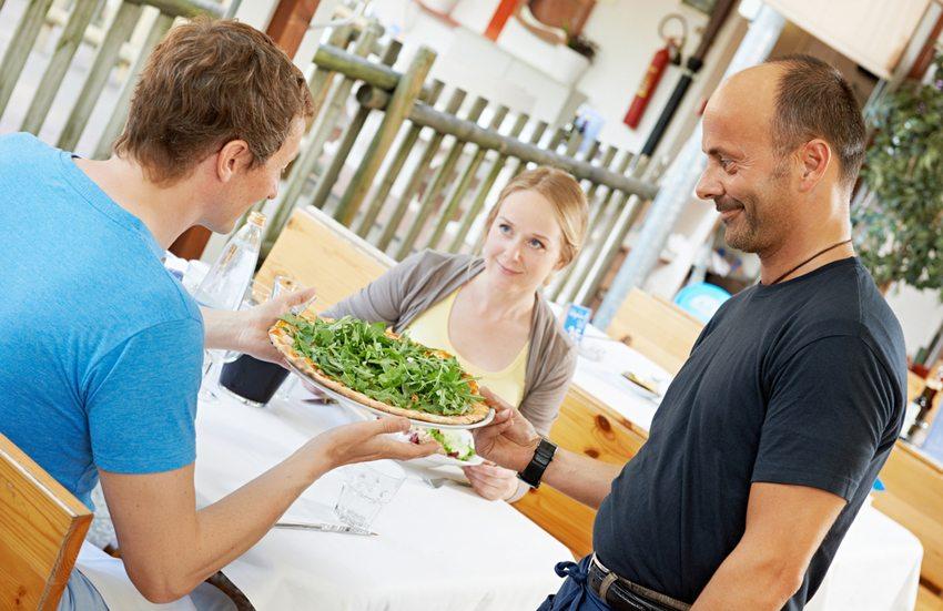 Italienische Pizza mit grünem Salat (Bild: Dmitry Kalinovsky / Shutterstock.com)
