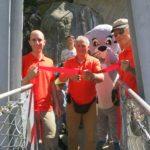 Reinhard Bittel, Präsident des Vereins Hängebrücke Aspi-Titter, schneidet an der Einweihung das Band durch. Dabei wird er vom Vize-Präsidenten Patrick Bizeau (links) und Kassier Peter Dittus flankiert. Bella wartet aufgeregt im Hintergrund. © aspi-titter.ch