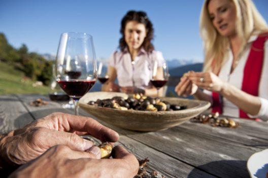 Nach einer herbstlichen Wanderung laden Buschenschänken zu geselligem Beisammensein, um bei Kastanien und Wein das Südtiroler Bergpanorama im Licht der letzten Sonnenstrahlen zu geniessen. (Bild: IDM Südtirol /Alex Filz)