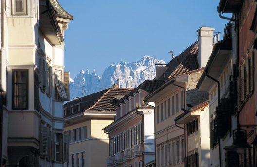 Imposant blicken die Bergsilhouetten und verschneiten Berggipfel hinter den Häusern der Bozner Altstadt hervor. (Bild: © Südtirol Marketing / Laurin Moser)