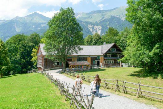 Besucher an einem alten Bauernhaus im Freilichtmuseum Ballenberg (Bild: © Stefano Ember - shutterstock.com)