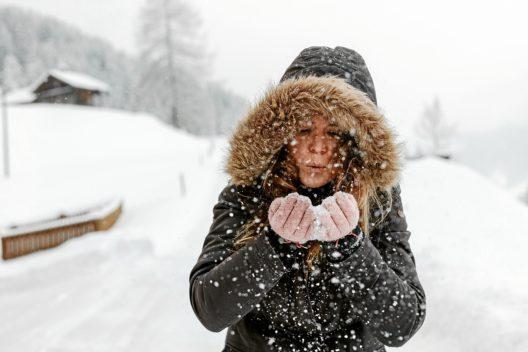 Junge Frau pustet Schnee von ihren Haenden. (Bild: © Adelboden Tourismus - swiss-image.ch/Anja Zurbruegg)
