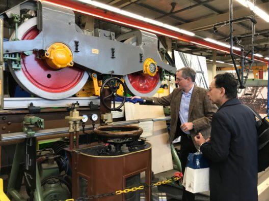 Ulrich Jaeger (Geschäftsführer WSW mobil GmbH) zeigt Hideo Otawari (Präsident Shonan Monorail) die Schwebebahnwerkstatt in Wuppertal-Vohwinkel. (Bild: obs/WSW Wuppertaler Stadtwerke GmbH/Shonan Monorail)
