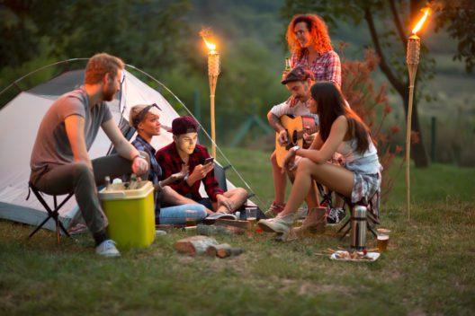 Jugendliche vor Zelt mit Bier, Gitarre und Schlagzeug nachts sozialisieren