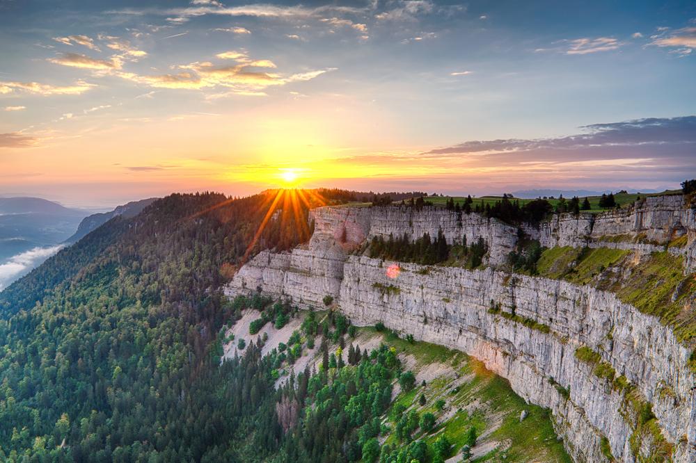 Lebendiger Sonnenuntergang mit Sonnenstern über der Klippe Creux du Van Neuchatel im warmen Licht mit Blick auf das Tal und den grünen Wald