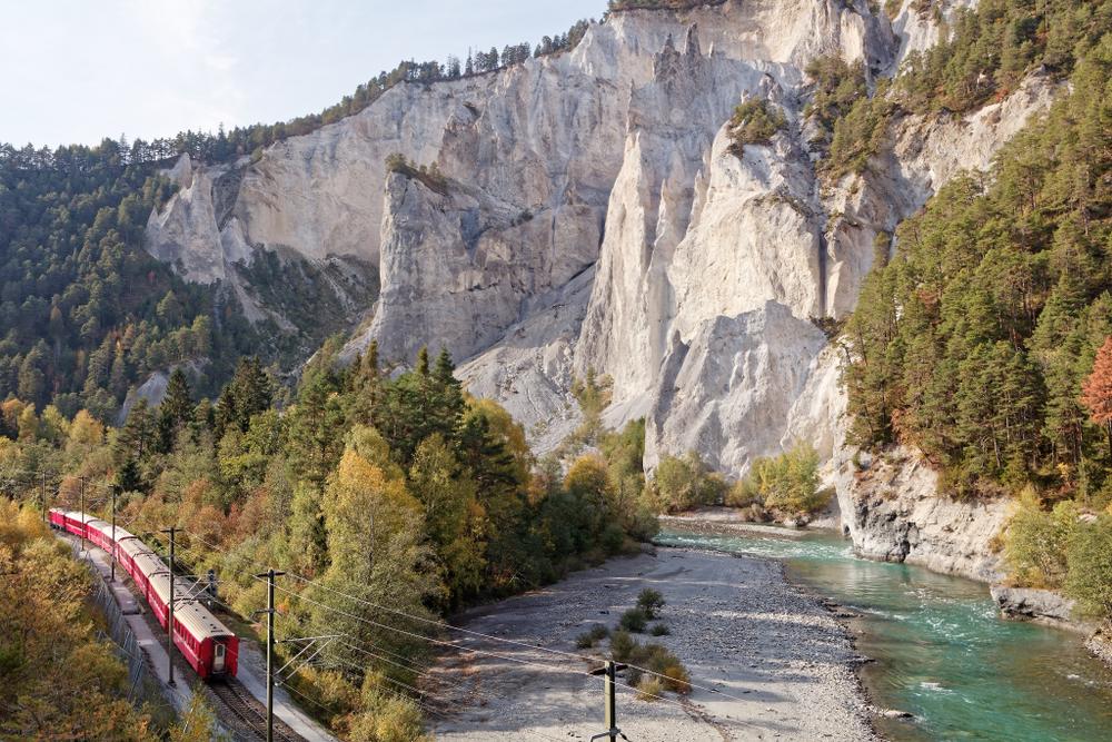 Vorbeifahrt mit dem Glacier-Express-Zug in der sonnigen herbstlichen Ruinaulta - Rheinschlucht bei Versam-Safien, Schweiz